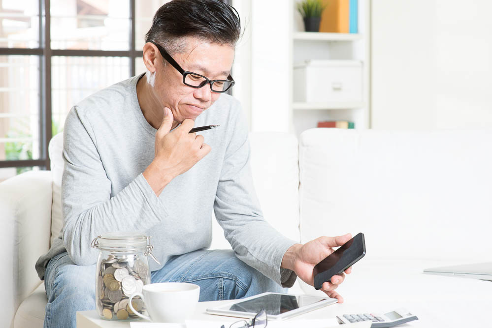 mature asian man sitting a desk with, looking at a tablet pc and smart phone