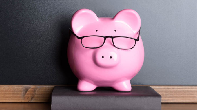 Piggy Bank With Eye Glasses On Book